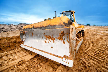 site: close-up of bulldozer blade, industrial machines working in sandpit on construction site