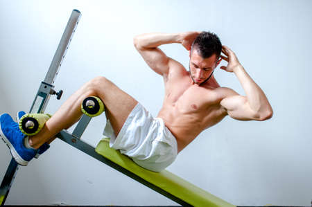 Handsome muscular man doing sit-ups on a incline bench at fitness center or gym photo