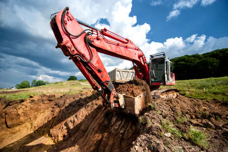 open cast mine: Excavator loading dumper truck tipper in sandpit in highway construction site and quarry Stock Photo