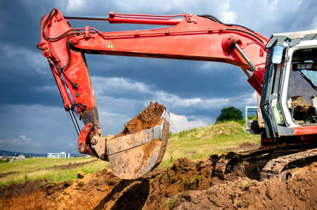 eathmover, industrial digger and excavator working in sandpit on construction site photo