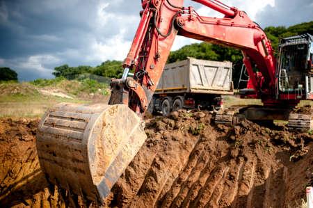 maquinaria pesada: excavadora de manutención de cavar un agujero y Tierra del cargamento en un camión dumper en una cantera o una obra en construcción Foto de archivo