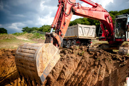 industrial excavator digging a hole and loading earth in a dumper truck at a quarry or a construction site Stock Photo