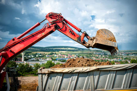 close-up of industrial excavator loading a dumper truck with soil and earth from construction site photo