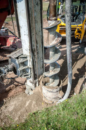 auger: Close up of construction auger, industrial drilling rig making a hole in the ground Stock Photo