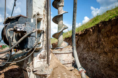 Close up of auger, industrial drilling rig making a hole in the ground