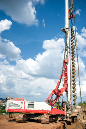 industrial construction site with drilling rig making holes in the ground Stock Photo