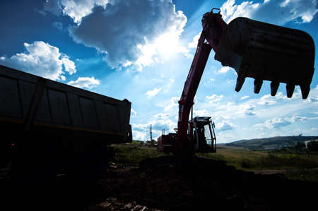 loading truck: silhouette of industrial excavator loading earth into a dumper truck at construction site
