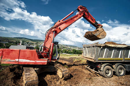 bulldozers: Industrial excavator loading soil material from highway construction site in a dumper truck