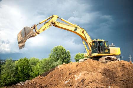 backhoe en industriële graafmachine werken in bouwwerf, steengroeve en het laden van de aarde in kipwagenvrachtwagen Stockfoto