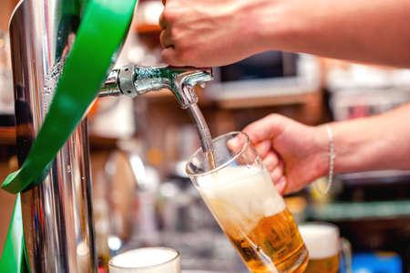 pilsner beer glass: close-up of barman brewing a draft beer at pub  Bartender pouring beer in a mug