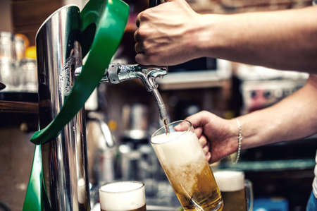 Barman pouring or brewing a draught beer at restaurant, bar or pub photo