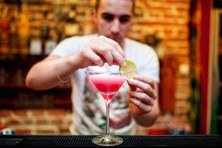 barman preparing cosmopolitan alcoholic cocktail drink at bar  Alcoholic drink with vodka, triple sec, cranberry juice and lemon juice