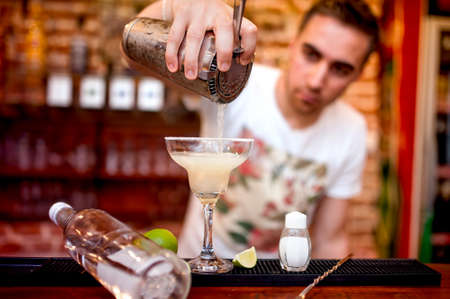 barman pouring a margarita alcoholic cocktail served in casino and bar photo