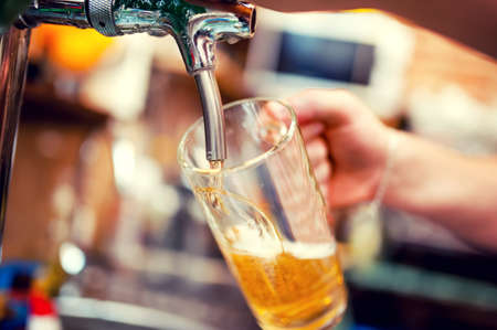 close-up of barman hand at beer tap pouring a draught lager beer 스톡 콘텐츠
