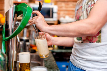 barman pouring a draught beer at pub or bar photo