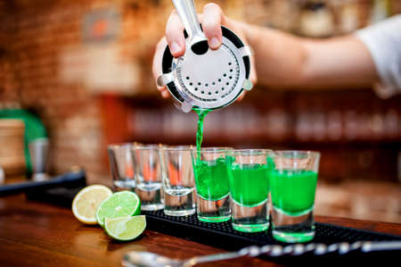 shooter drink: Close-up of bartender hand pouring alcoholic drink in restaurant, pub or bar