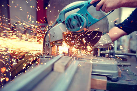 industrial engineer working on cutting a metal and steel with compound mitre saw with sharp, circular blade