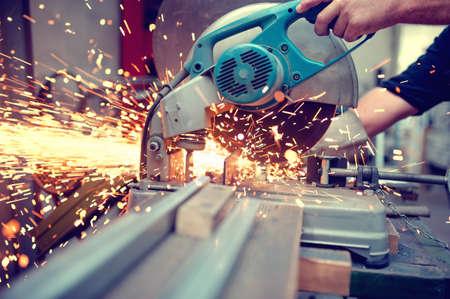 Wirtschaftsingenieur arbeitet an Schneid ein Metall und Stahl mit Verbindung Gehrungssäge mit scharfen, Kreismesser