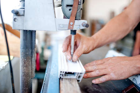 screwing: worker and handyman using an industrial tool for screwing in metal and plastic. Industrial metal milling and steel manufacturing