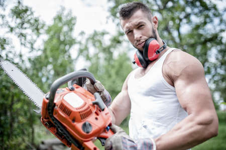 portrait of aggressive muscular male lumberjack, woodworker with chainsaw in hand, posing photo