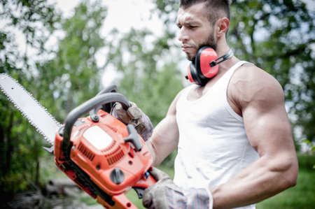 portrait of angry muscular male lumberjack, woodworker with chainsaw in hand, posing  photo