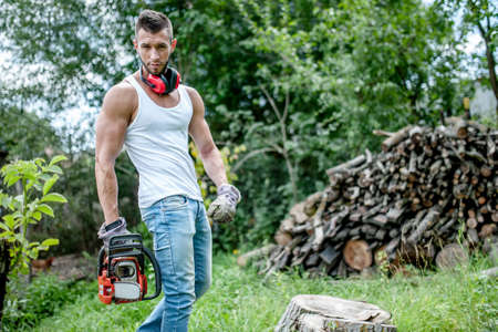 portrait of expressive muscular lumberjack, man with chainsaw and tank top in forest photo