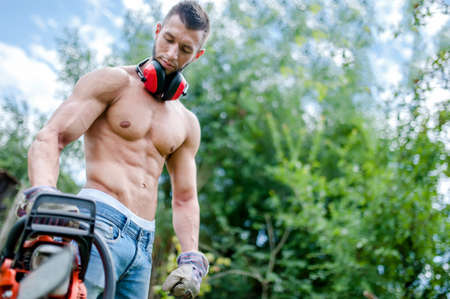 portrait of agressive athletic man with chainsaw getting ready for fire wood cutting  photo