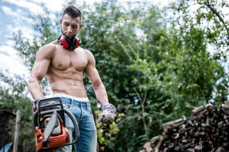 timber cutting: portrait of sexy man with chainsaw and protective gear ready for cutting wood