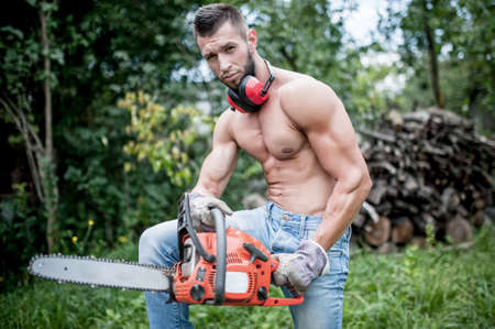 portrait of handsome athletic man with chainsaw and protective gear ready for cutting wood photo