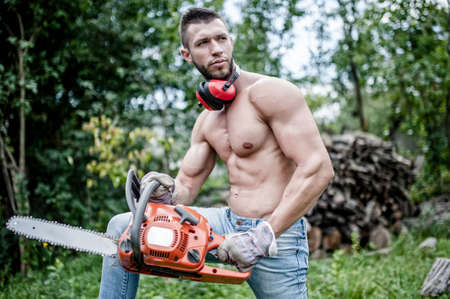 portrait of handsome muscular man with chainsaw and protective gear ready for cutting wood photo