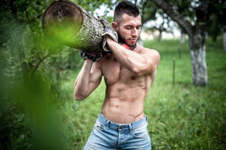 male model carrying and cutting wood logs for firewood  photo