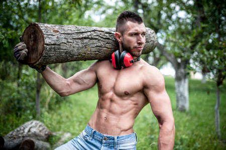 male arm: handsome male model moving logs, cutting firewood and posing