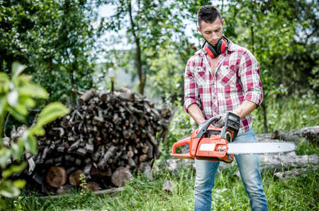 portrait of aggressive, muscular and athletic man with chainsaw getting ready for fire wood cutting photo