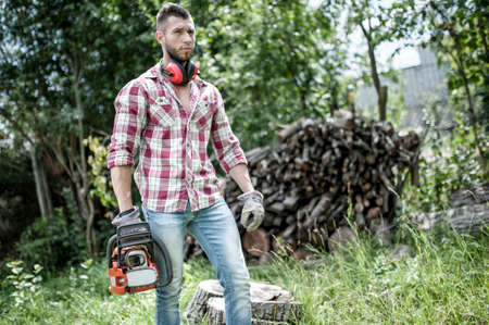 woodcutter: lumberjack or woodcutter moving and looking with chainsaw for trees to chop Stock Photo