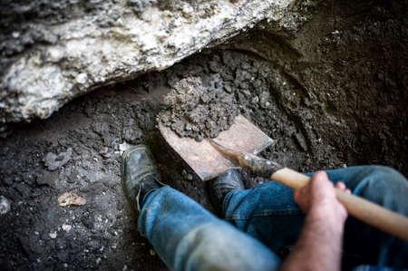 man het graven van een gat in de grond met schop en spade