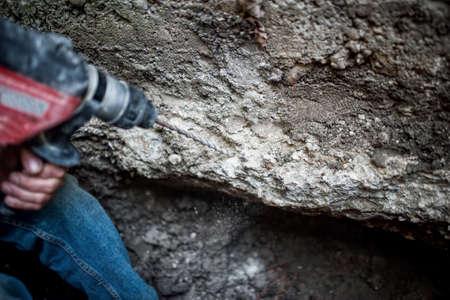 presslufthammer: Mann mit Bohrmaschine Zerstörung einer dicken Betonwand in Baustelle Lizenzfreie Bilder