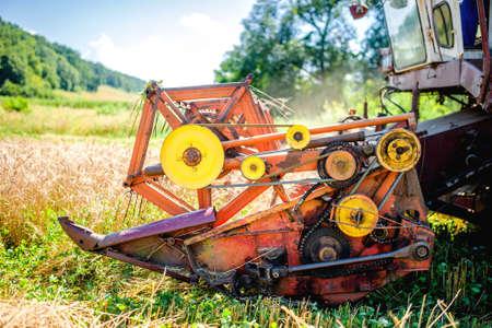 cosechadora: Detalle de la maquinaria cosechadora, tractor en la granja con la cosechadora recolección de los cultivos de granos maduros Foto de archivo