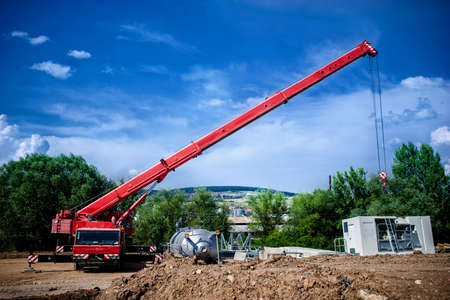 Industrial Crane operating and lifting an electric generator and concrete mobile station against sunlight and blue sky