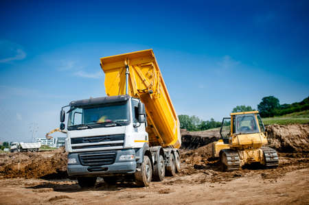 dumper truck and bulldozer at highway road construction site 스톡 콘텐츠