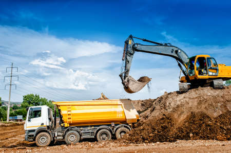 Industrial truck loader excavator and bulldozer moving earth and unloading into a dumper truck