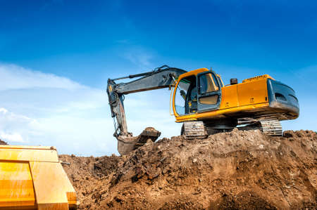 earth moving: construction site digger, excavator and dumper truck  industrial machinery on building site