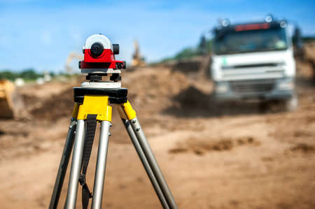 cartographer: surveyor engineering equipment with theodolite at highway infrastructure construction site