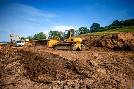 industrial machinery at working construction building site  Excavator, dumper truck and bulldozer working on ground