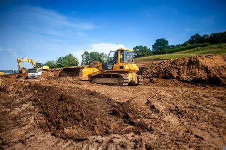 maquinaria industrial en el trabajo construcción edificio excavadora, camión volquete y excavadora trabajando en terreno Foto de archivo