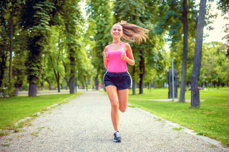 healthy and happy woman running in urban park with headphones and music  photo