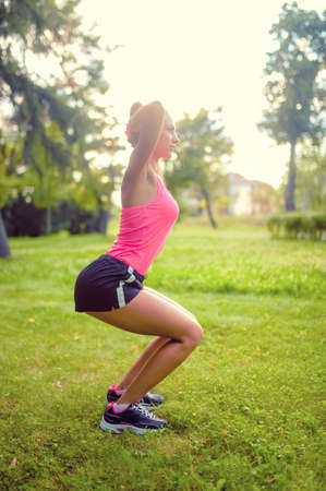 skinny woman in park, doing squats and running at sunset  fitness training and workout photo