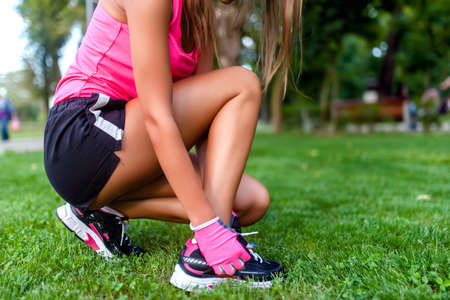 Close-up of active jogging female runner, preparing shoes for training and working out at fitness park photo