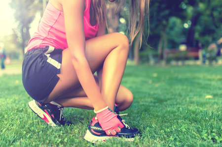 jogging track: Close-up of active jogging female runner, preparing shoes for training and working out at fitness park