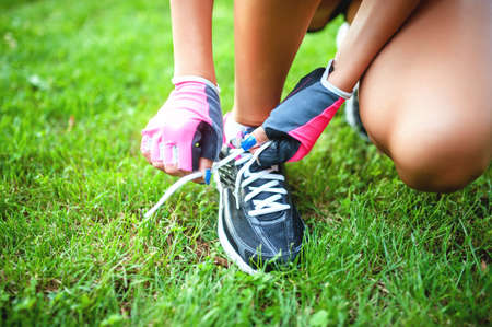 female runner and athlete preparing shoes for jogging photo