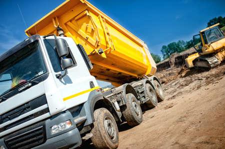 volteo: camión volquete en el sitio constrution industrial a la espera de la carga de la tierra excavadora Foto de archivo